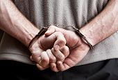 stock photo of hooligan  - Criminal hands locked in handcuffs - JPG