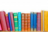 stock photo of book-shelf  - Used grunge colourful books at library shelf - JPG