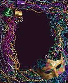 foto of mardi gras mask  - A group of Mardi Gras beads and mask making a frame with copy space on a purple background - JPG