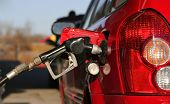 pic of bowser  - cropped photo showing a bowser hose filling a car with gasoline or petrol.