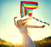 Beauty girl in short dress running with kite on the field. Beautiful young woman with flying colorfu poster