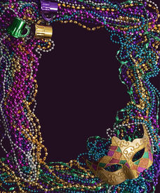 stock photo of mardi gras mask  - A group of Mardi Gras beads and mask making a frame with copy space on a purple background - JPG