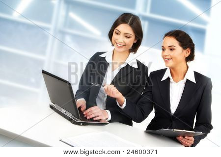 Creative image of two businesswomen working with laptop in office