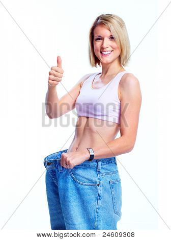 Happy young woman with big jeans. Weight loose. Isolated over white background.