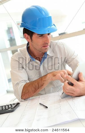 Smiling architect in office working with electronic tablet