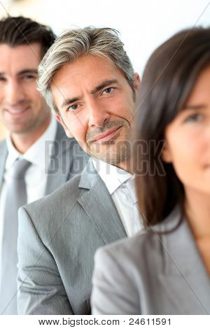 Smiling businessman standing amongst group