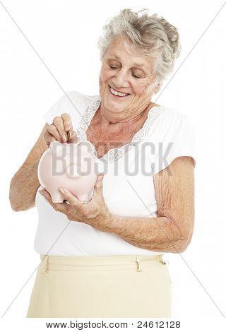 Retrato de mujer mayor ahorro moneda en la alcancía sobre blanco