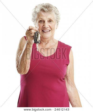 portrait of senior woman holding car keys over white background