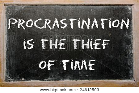 "Proverb ""procrastination Is The Thief Of Time"" Written On A Blackboard"