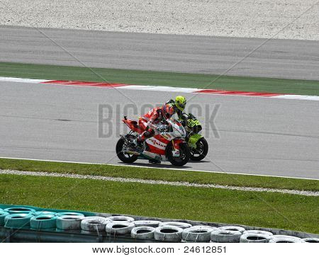 SEPANG, MALAYSIA - OCTOBER 23: Moto2 riders Stefan Bradl (65) and Andrea Iannone (29) test out each other during warm-up of the Malaysian Motorcycle GP 2011 on October 23, 2011 at Sepang, Malaysia.