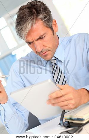 Manager in office using electronic tablet