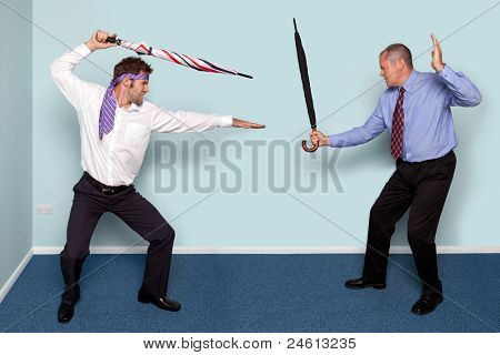 Photo of two businessmen having a sword fight using umbrellas, good image to convey conflict, rivalry or disagreement.
