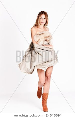 young woman in  flying dress with fur and high heel boots, studio shot, full body shot