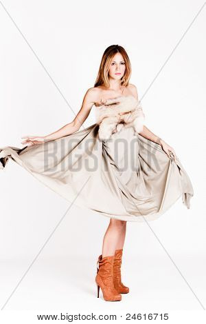 young woman in long flying dress with fur and high heel boots, studio shot, full body shot