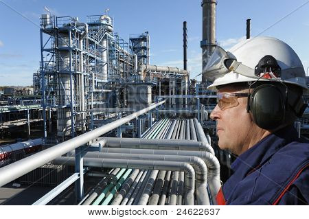 refinery worker with large petrochemical industry in background
