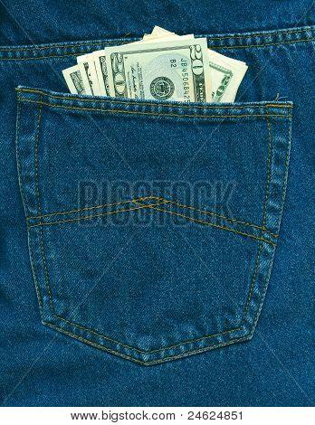 Dólares en el bolsillo de los pantalones vaqueros