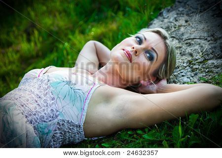 attractive woman lying on stones