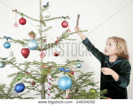 Christmas time - little girl decorating a Christmas tree