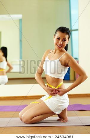 Portrait of happy fit female measuring her waist
