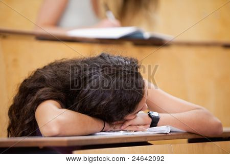 Student sleeping on her desk in an amphitheater