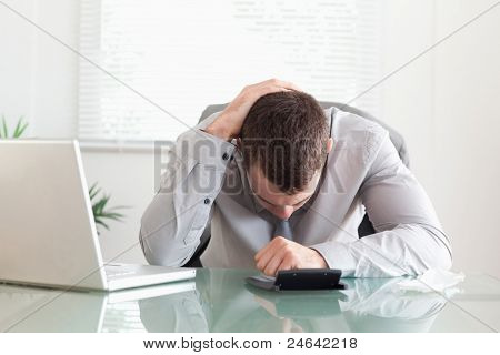Young businessman unhappy with his calculations