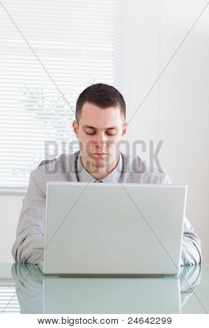 Close up of young businessman working on his laptop