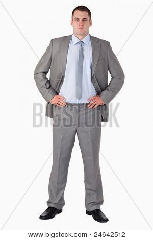 Businessman with arms akimbo on white background