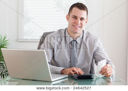Smiling young businessman checking an invoice