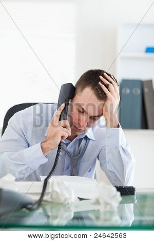 Close up of frustrated businessman looking at an invoice while on the phone