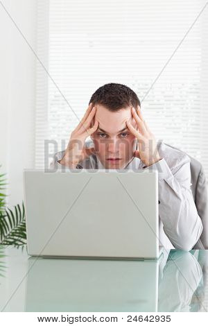 Close up of disappointed young businessman getting bad news via email