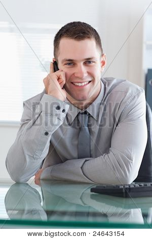 Businessman getting a pleasant call on his cellphone