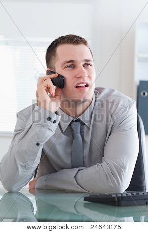 Young businessman looking at the screen while listening to the caller