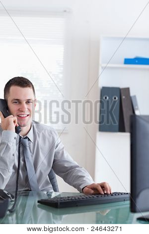 Smiling businessman listening to caller while typing