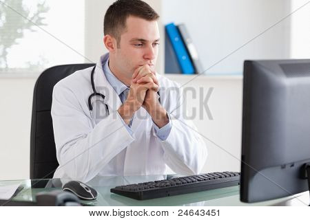 Thinking young doctor looking at his screen