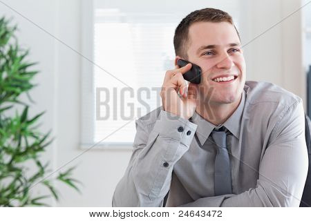 Smiling businessman getting a pleasant call on his mobile phone