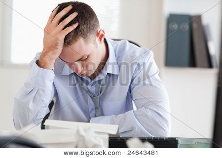 Young businessman stressed while doing his accounting