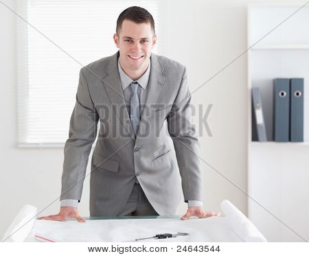 Smiling architect standing behind a table with plans in front of him