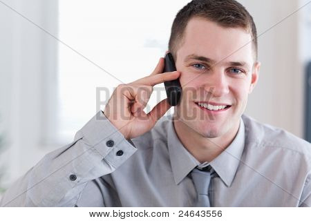 Smiling young businessman getting good news on the phone