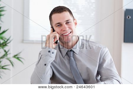 Smiling businessman getting pleasant news on the mobile phone