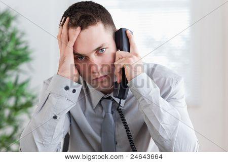 Empresário decepcionado recebendo más notícias no telefone