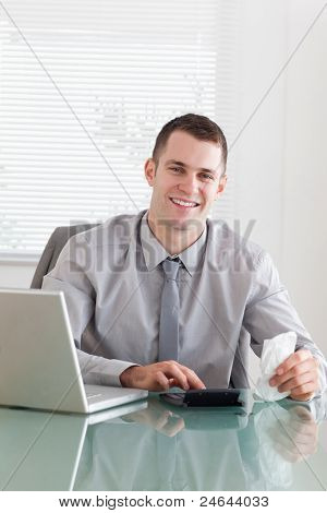 Happy young businessman checking an invoice