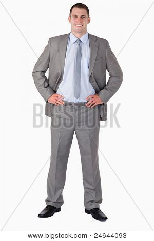 Smiling businessman with arms akimbo on white background