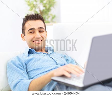Smiling young man working on laptop computer at home