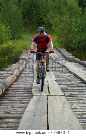 Mountain Biker Goes On Old Bridge