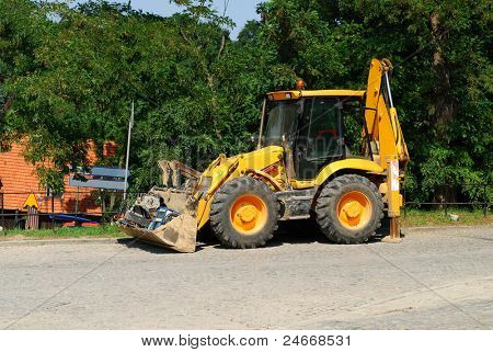 Wheel loader machine unloading sand at eathmoving works in construction site.