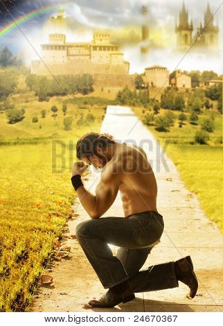 Conceptual portrait of a shirtless man kneeling with a dreamy fantastical background far behind