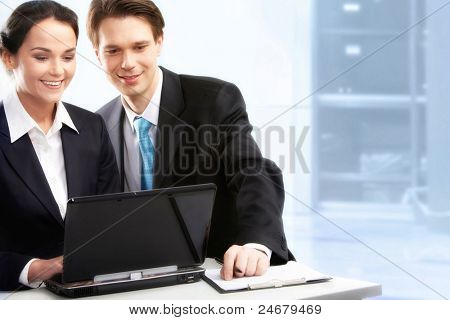 Creative image of two partners working with laptop in office