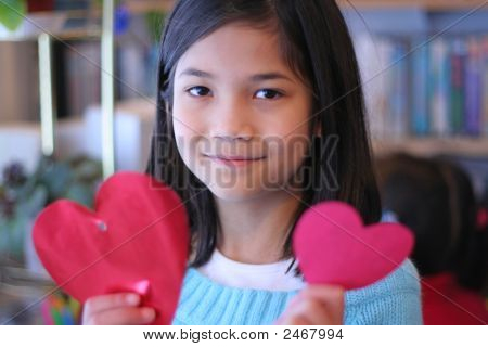 Nine Year Old Girl Holding Up Two Red Hearts.