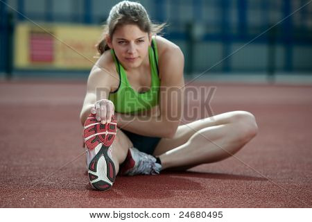 Young Female Sprinter Stretching