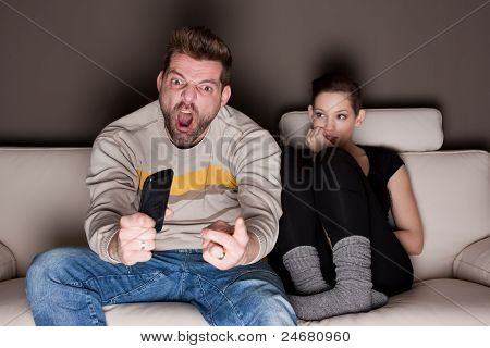 A Man Watching A Game, While His Girlfriend Is Sitting Besides Him Bored. Showing The Differences Be